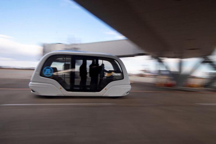 This photo shows several people inside an automated vehicle on the tarmac of an airport. The vehicle is moving left to right and is going to pass under an airport jet bridge.