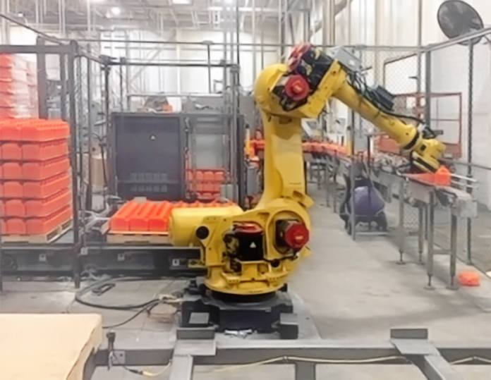 This image shows a yellow robot arm in the new Permatex facility.
