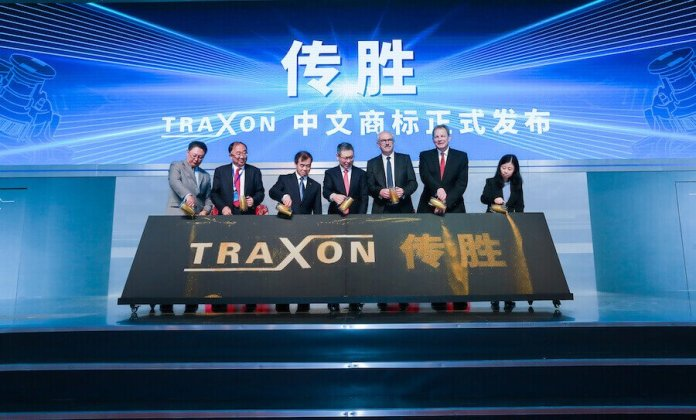 Several people are seen standing in front of a sign that says Traxon during a ceremony.