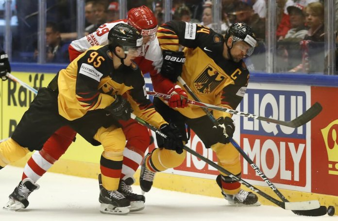 This image shows several hockey players battling for a puck on the ice. The LIQUI MOLY logo can be seen on the boards in the background.