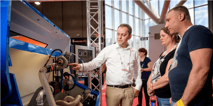 This image shows an exhibitor at the ReMaTec show demonstrating technology to two attendees of the show.