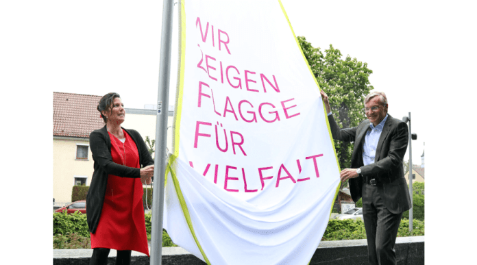 This photo shows two people holding a flag celebrating diversity. The flag's text is in German.