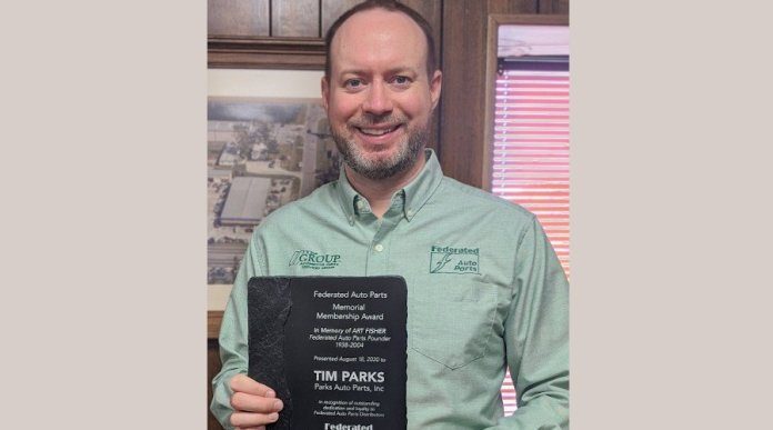 """This is a photo of Tim Parks. He has a beard and is smiling. He is wearing a green button-down shirt. He is holding an award that says, in part, """"Federated Auto Parts Memorial Membership Award, in memory of Art Fisher, Federated Auto Parts Founder. Presented to Tim Parks."""""""