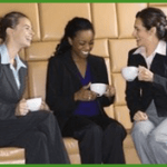3 women laughing and drinking coffee photo