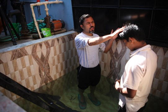 Pastor Tej baptizing church member