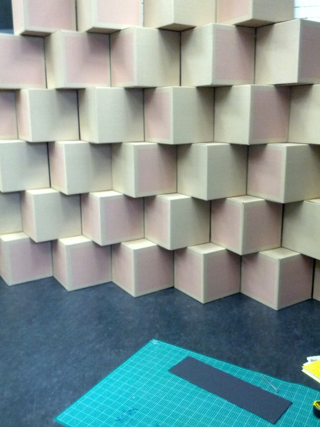 Over 200 recycled boxes were used to construct two walls on which photo essays were mounted