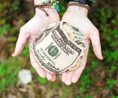 Photo of crumpled up 100 dollar bills