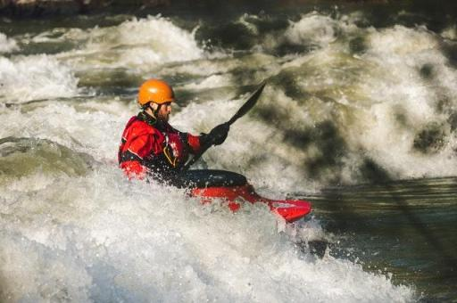 Photo of a man kayaking in the rapids