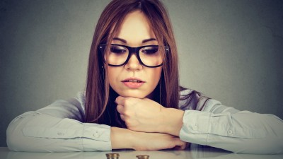 Ambitious business woman looking at growing stack of coins
