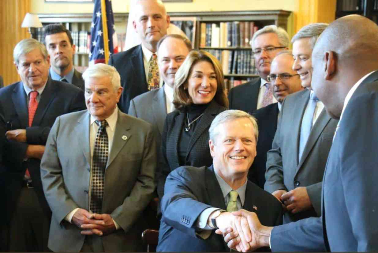After signing bill, Massachusetts Governor Charlie Baker congratulating legislators and family members who supported the hands free driving law banning holding cell phones while driving.