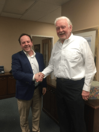 Picture of Henry Risman, President of the Risman Agencies and Thomas Ward, Owner of the T.F. Ward Insurance Agency shaking hands after signing the sale documents completing the acquisition of the Ward Agency by the Risman Agencies.