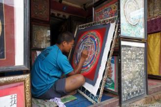 Un artista dipinge un mandala in uno studio a Changu Narayan