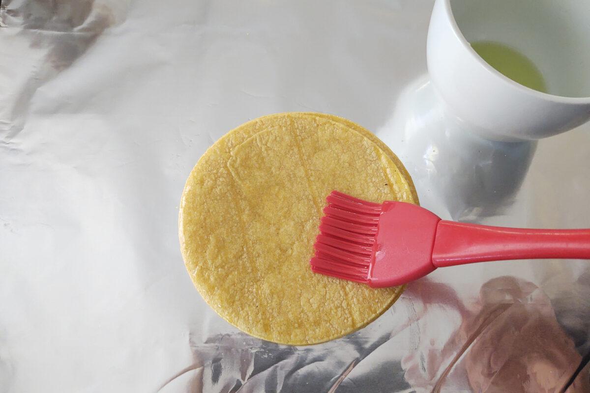 corn tortilla being oiled
