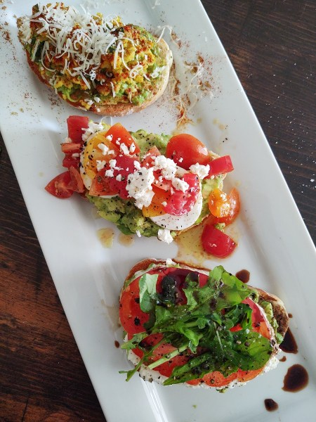 Three different types of avocado toast displayed vertically