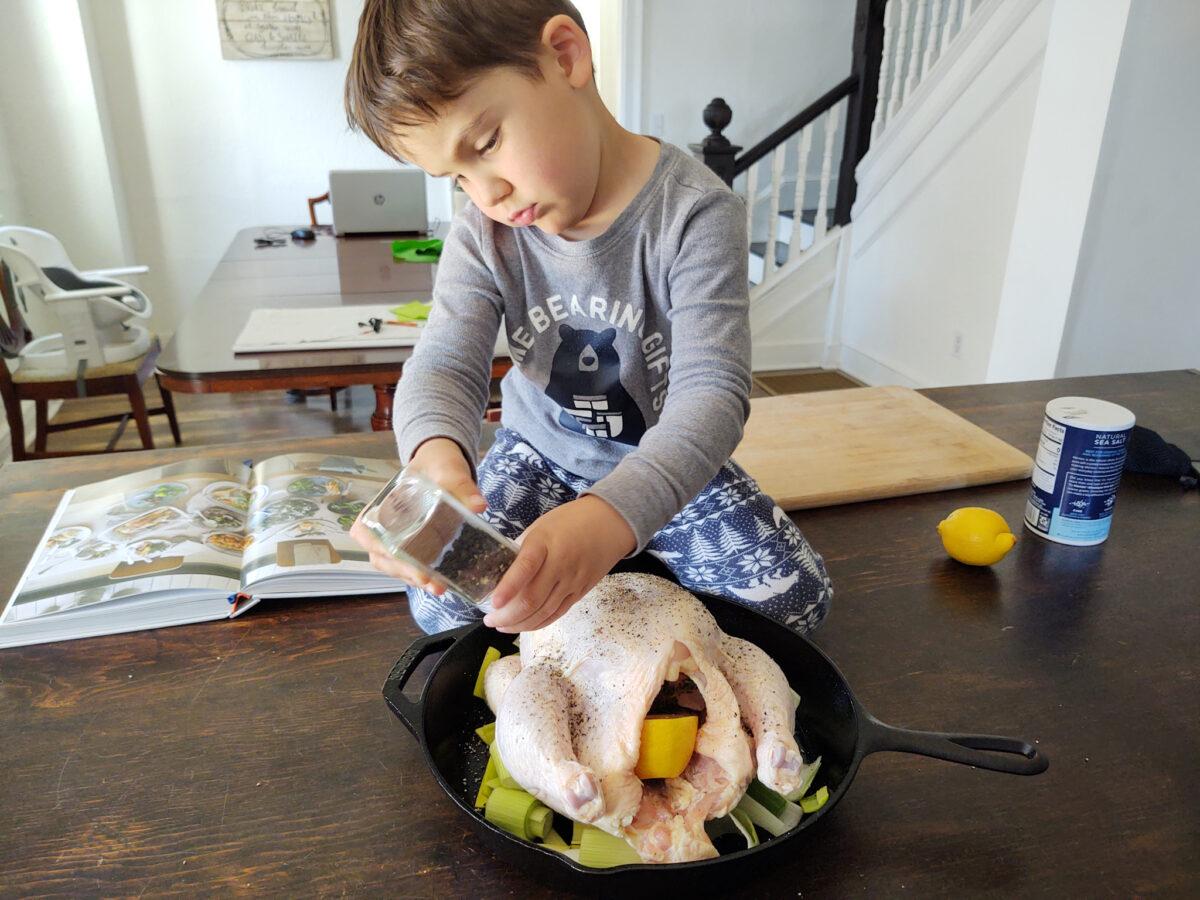 A boy cracking black pepper onto a chicken