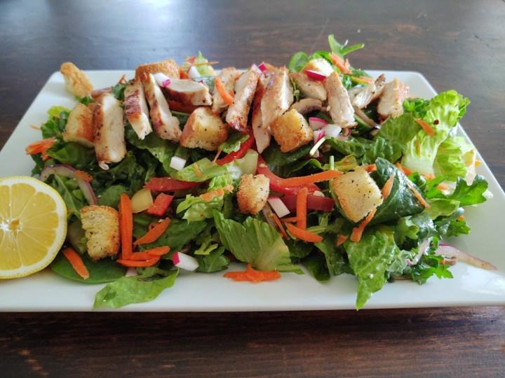 Horizontal shot of mixed green garden salad with chicken