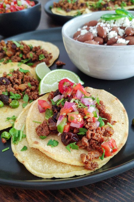 Display of Chorizo Tacos with a side of beans and Pico de Gallo Salsa