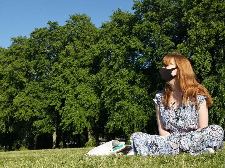 A girl sitting on grass in a Paisley patterned dress and wearing a face covering while looking off to the distance. This is Gail, the author.
