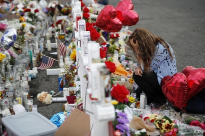 Gloria Garces kneels in front of crosses at a makeshift memorial near the scene of a mass shooting at a shopping complex Tuesday, Aug. 6, 2019, in El Paso, Texas. The border city jolted by a weekend massacre at a Walmart absorbed more grief Monday…