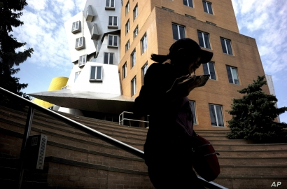 In this Tuesday, July 16, 2019 photo a passer-by appears in silhouette while walking past the Ray and Maria Stata Center, behind, on the campus of Massachusetts Institute of Technology, in Cambridge, Mass. (AP Photo/Steven Senne)