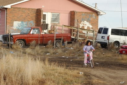 In this file photo, a young Lakota girl rides her bike on Pine Ridge Indian Reservation in southwestern S.D. on Tuesday , Jan. 10, 2006. At least 60% of Pine Ridge homes are substandard, lacking electricity, running water or sewage systems. (AP Photo...