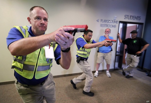 Police officers David Riggall, left, and Nick Guadarrama, center, demonstrate to students Stephen Hatherley, center rear, and Chris Scott, right rear, how to clear a hallway intersection during a security training session at Fellowship of the Parks campus in Haslet, Texas, July 21, 2019.