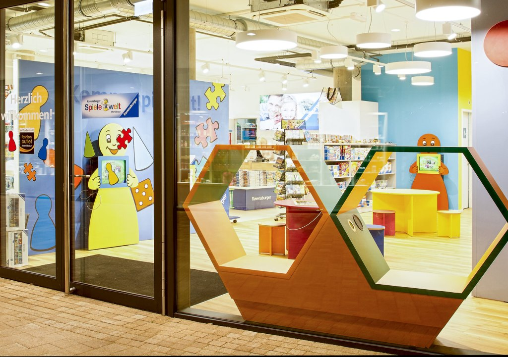 Kulissenwand mit Kinder-Touch-Computer und Labyrinth-Spieltisch.