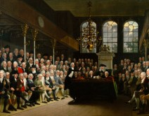 A painting showing the inside of the house of commons, the room is full of well dressed men with white hair. In the centre of the room is a table and a man can be seen speaking to the room.