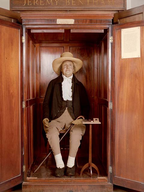 a photo of an wax figure dressed in eighteenth century clothes in a wooden cabinet
