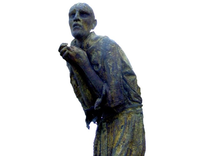 A photograph of a statue depicting a gaunt looking man, he is cowered over with his hands in a begging position and his eyes look sunken and scared.