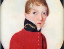 A miniature, oval portrait of a young soldier dressed in red military uniform and looking towards the viewer. The soldier has strawberry blonde curly but short hair
