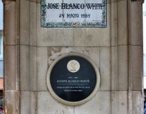 A photograph of a stone memorial with two plaques. At the top is a floral, tiled, blue and white plaque and beneath it is a circular black plaque. Both read the name 'Joseph Blanco White'