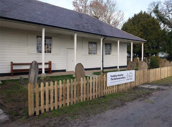 a photo of a wood clapperboard building with porch veranda and gravestones out front