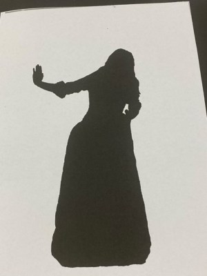 silhouette of figure in long dress holding out hand