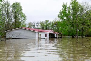 Flood waters surround the bottom third of a mobile home with trees in the background.