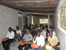 AggreBind instructing construction engineers and laborers in Tabarre HAITI on how to make blocks and roads with AggreBind & in situ materials
