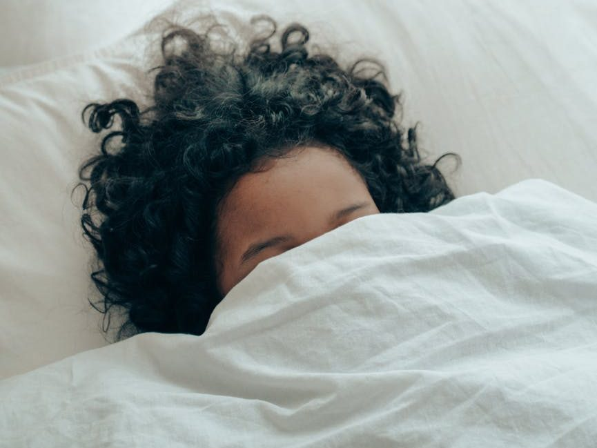 unrecognizable person sleeping under blanket