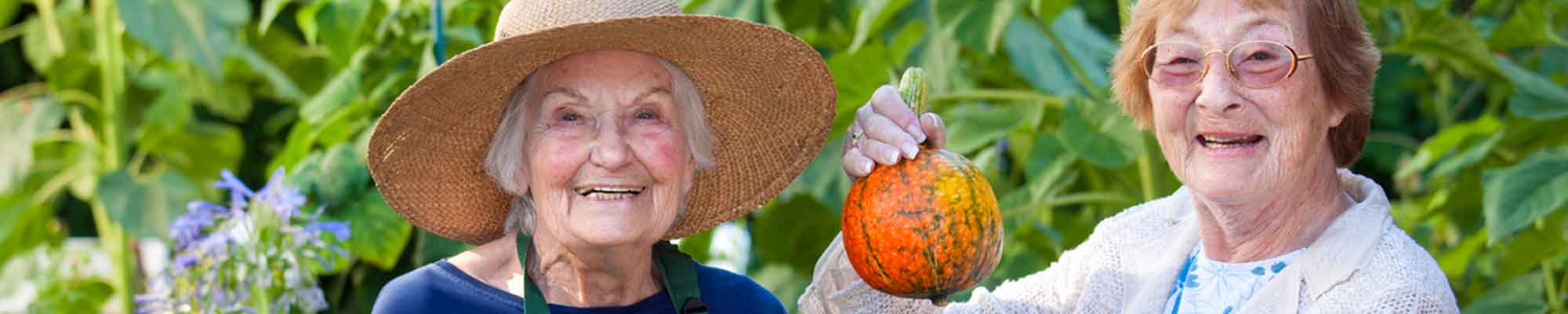 Two Aging Women in a Garden with Orange Squash