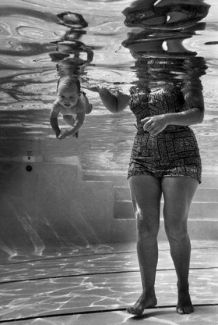 World's youngest swimmerJulie Sheldon, 9 weeks old, swimming underwater next to her grandmother Mrs. Jen Loven, a children's swimming instructor, recorded by photographer through underwater window of the Lovens'r outdoor pool.