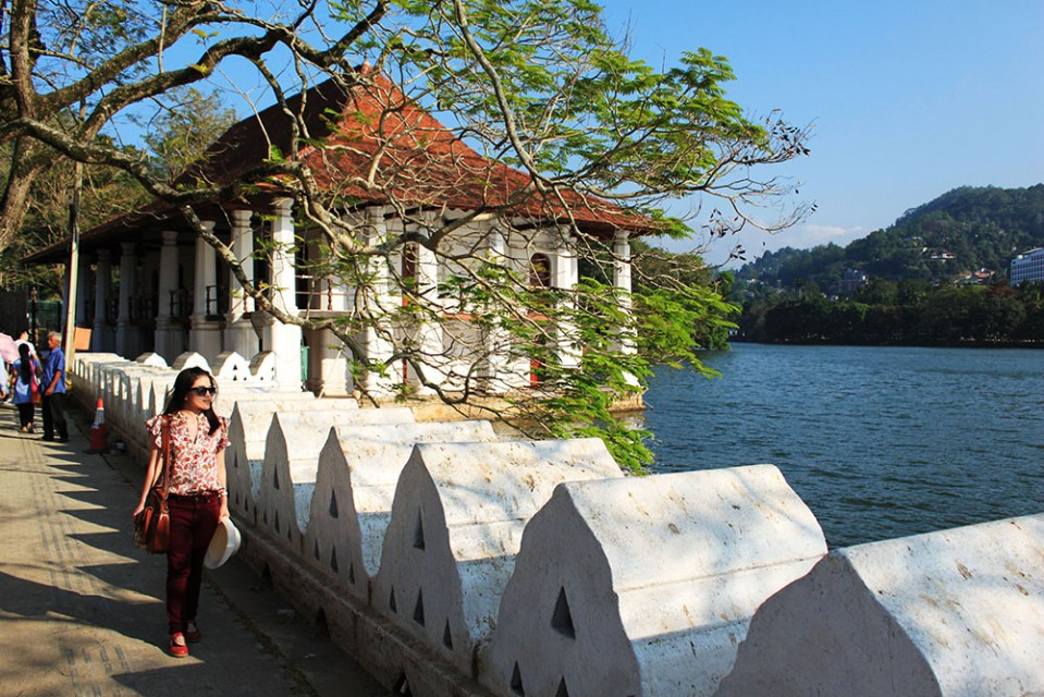 female solo traveler walking outside the temple of the sacred tooth relic sri lanka