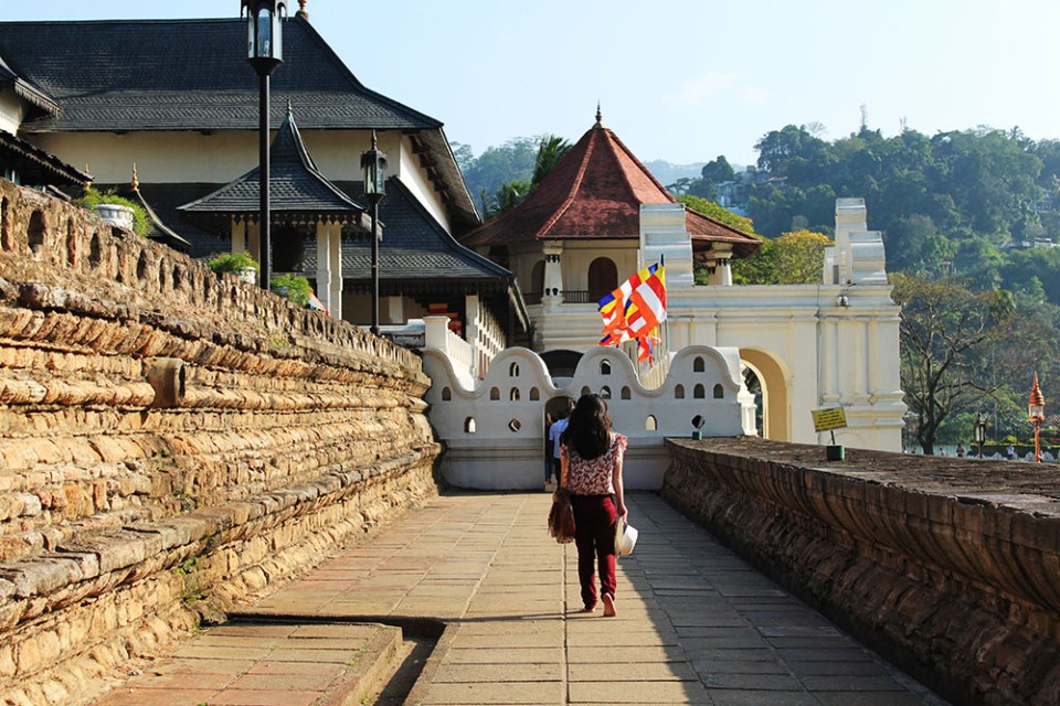 a female traveller walking barefooted in The Temple of the Sacred Tooth Relic, Sri Lanka