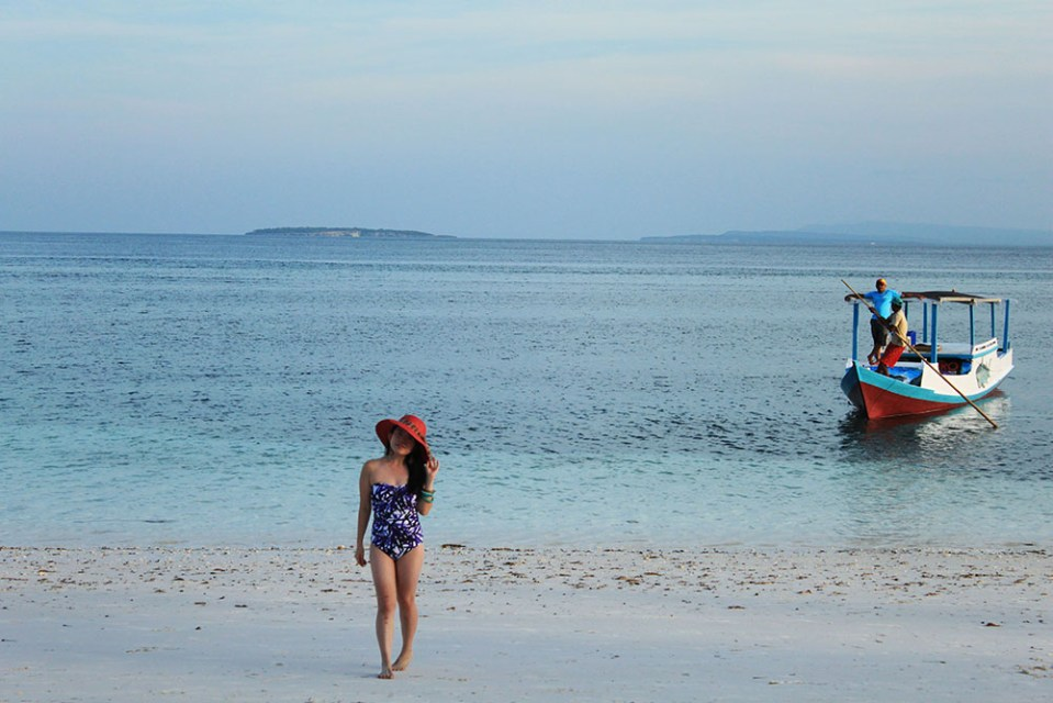 a girl with big red hat and swimsuit in Tanjung Bira beach during summer holiday near BaraCoco Bungalows