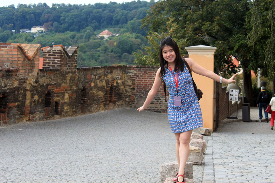 A playful girl walking on Czech cobbled stone after investing for her bucket list