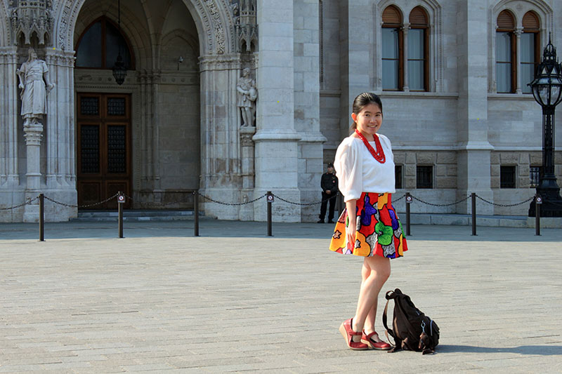 a little girl white top colorful skirt in front of Hungary Parliament Building