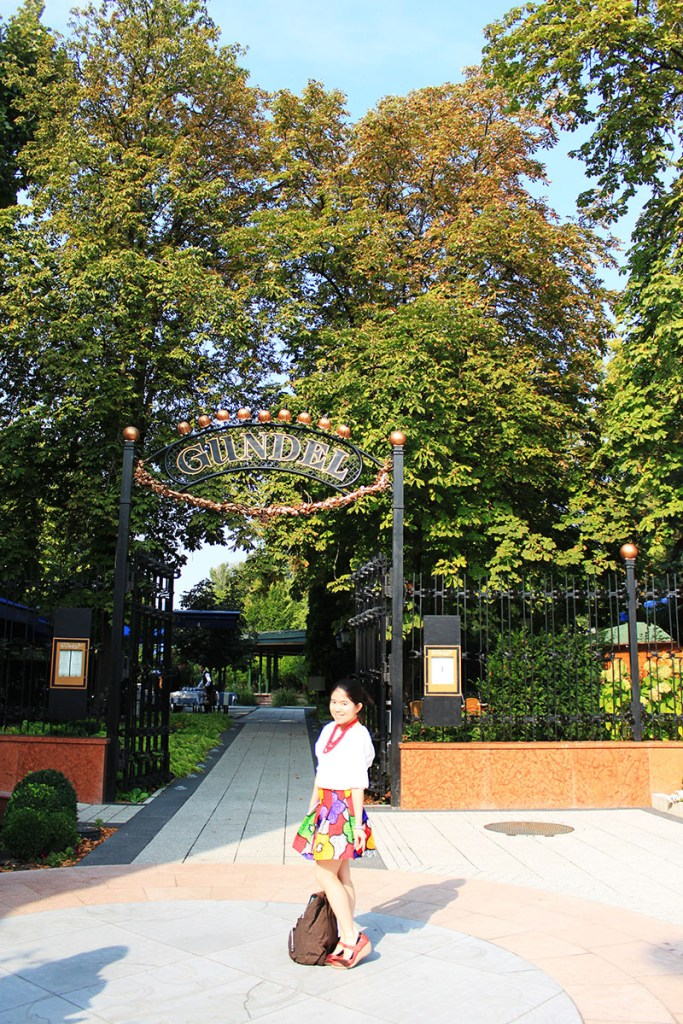 a girl standing in front of Gundel Budapest garden beautiful park entrance