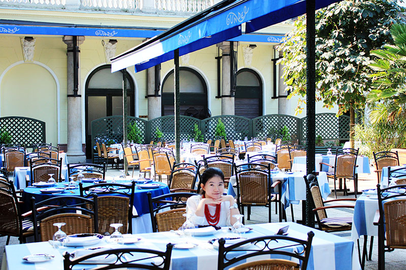 girl with red necklace sitting at Gundel restaurant Budapest garden blue white canopy breakfast