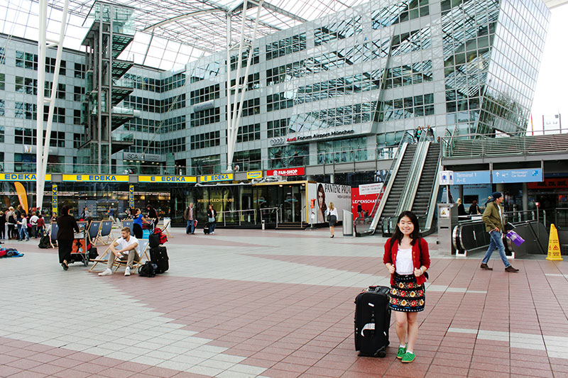 asian tourist traveler girl red cardigan floral skirt oktoberfest green munich airport gemany