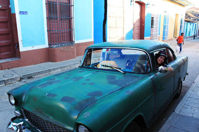 female solo traveler smile happy peak out cuba old taxi car