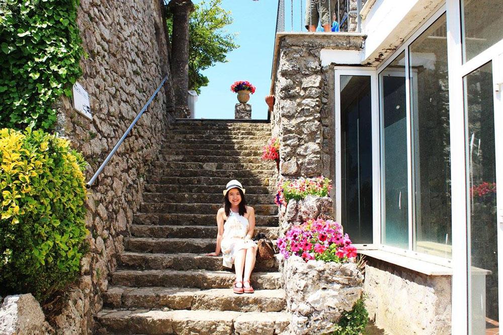 agirlnamedclara female asian traveler white dress hat sits staircase italy capri amalfi coast flower sunshine