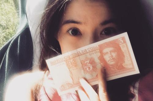 girl holds cuban pesos che gueavara pink clothes